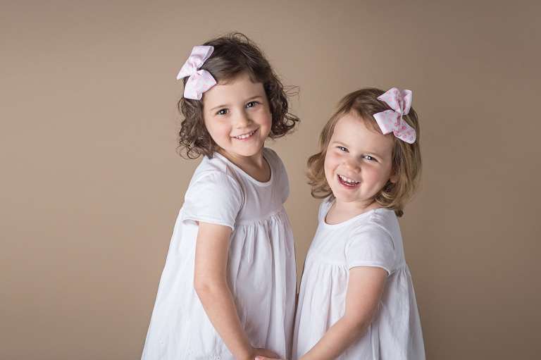 children smiling while holding hands in white dresses Louisville CO