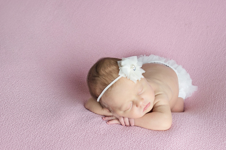 newborn girl on pink blanket contact photographer